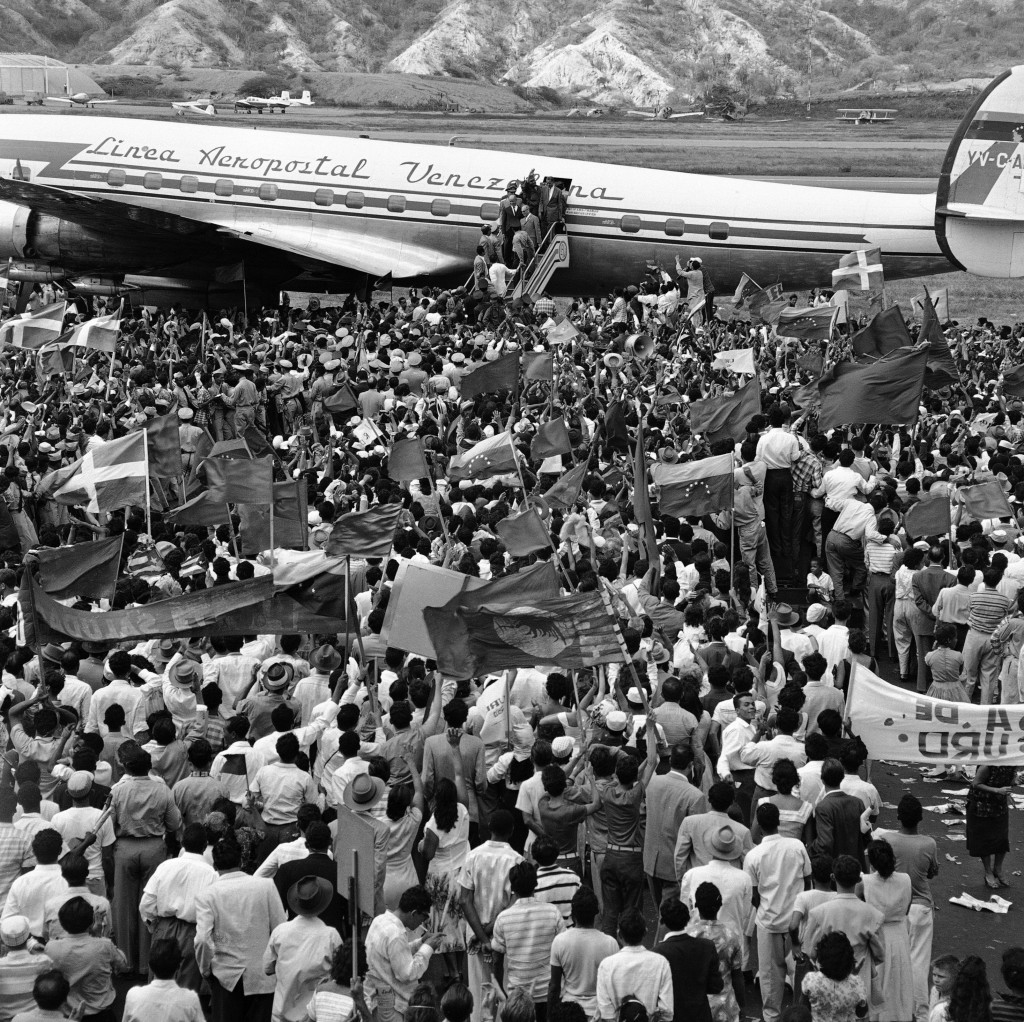 FILE - In this Jan. 23, 1959 file photo, a crowd estimated at more than 20,000 greet Cuban leader Fidel Castro as he waves from a plane upon arrival t
