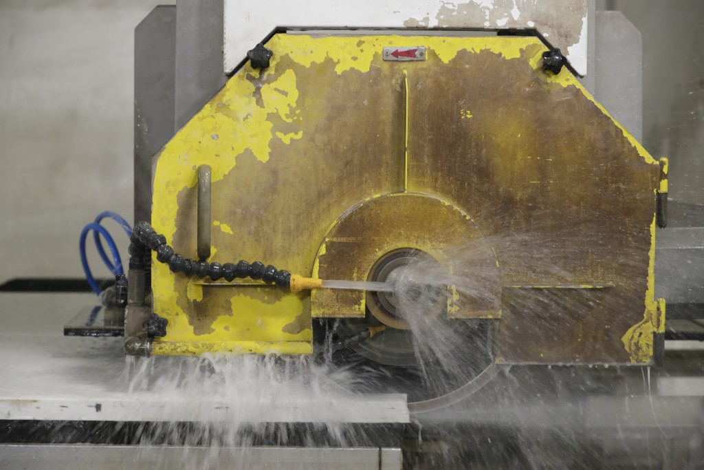 A computer operated wet saw cuts though an imported quartz slab from China as they begin production on a kitchen countertop at Marble Uniques in Tipto...