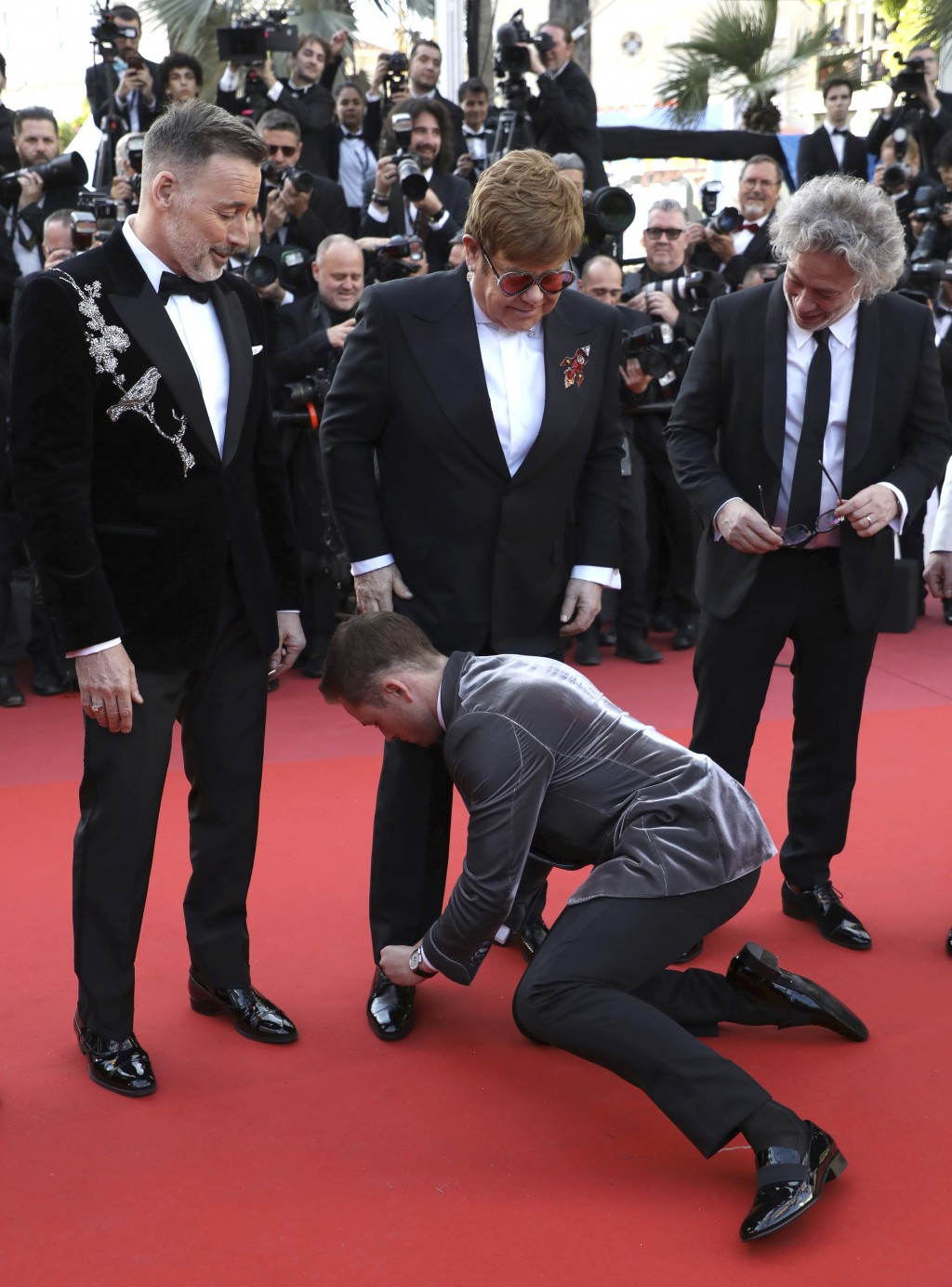 Actor Taron Egerton, center, ties the shoelaces of singer Elton John, center top, as they pose with producer David Furnish, director Dexter Fletcher,