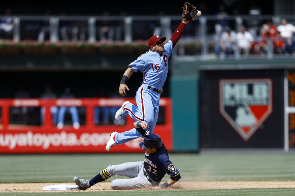 Milwaukee Brewers' Christian Yelich, bottom, steals second base as Philadelphia Phillies second baseman Cesar Hernandez leaps for the overthrow during