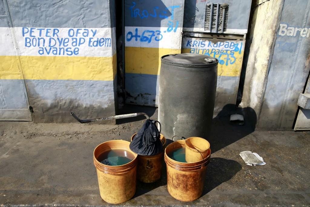 In this April 16, 2019 photo, open containers full with fuel stand on the sidewalk to be sold near the Thor terminal in Carrefour, a district of Port-