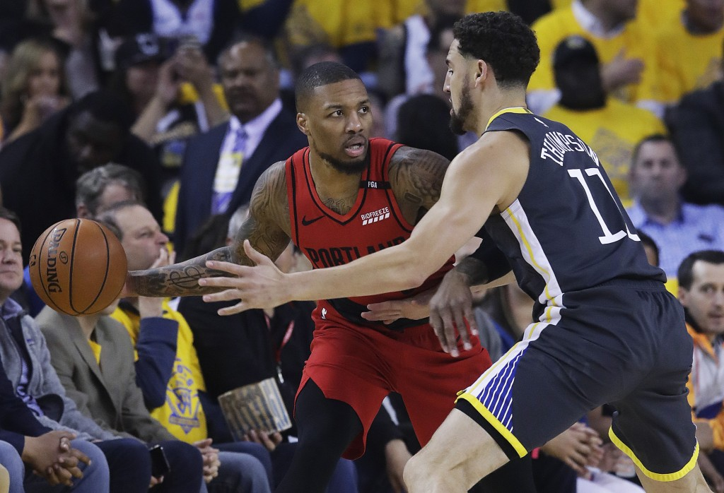 Portland Trail Blazers guard Damian Lillard, left, is defended by Golden State Warriors guard Klay Thompson during the first half of Game 2 of the NBA