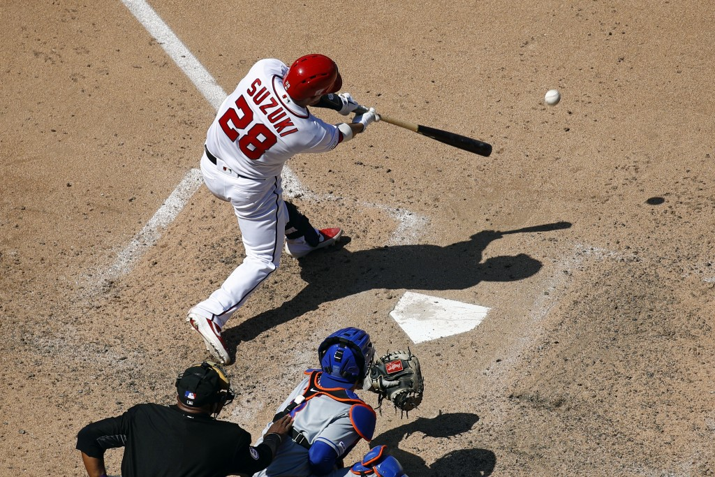 Washington Nationals' Kurt Suzuki singles in front of New York Mets catcher Tomas Nido and umpire Laz Diaz in the seventh inning of a baseball game, T
