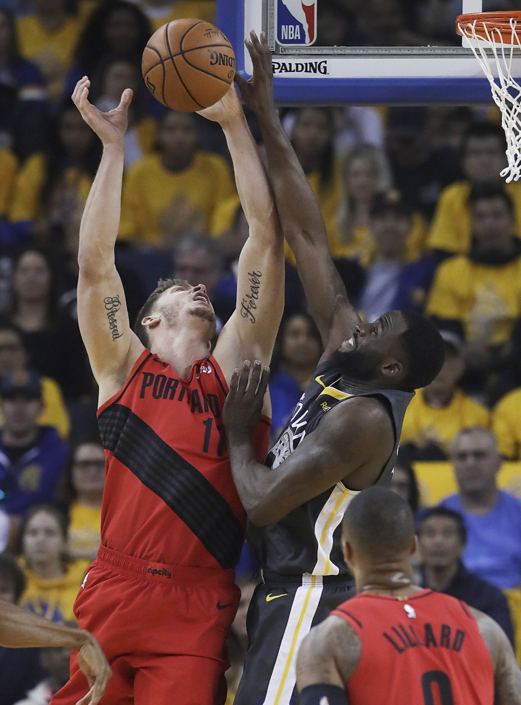 Golden State Warriors forward Draymond Green, top right, defends a shot by Portland Trail Blazers forward Meyers Leonard during the first half of Game
