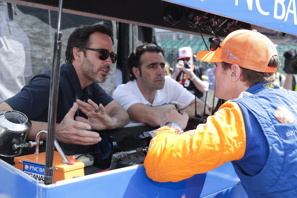 Scott Dixon, of New Zealand, talks with NASCAR driver Jimmy Johnson, left, and three-time Indy 500 champion Dario Franchitti, center, during practice