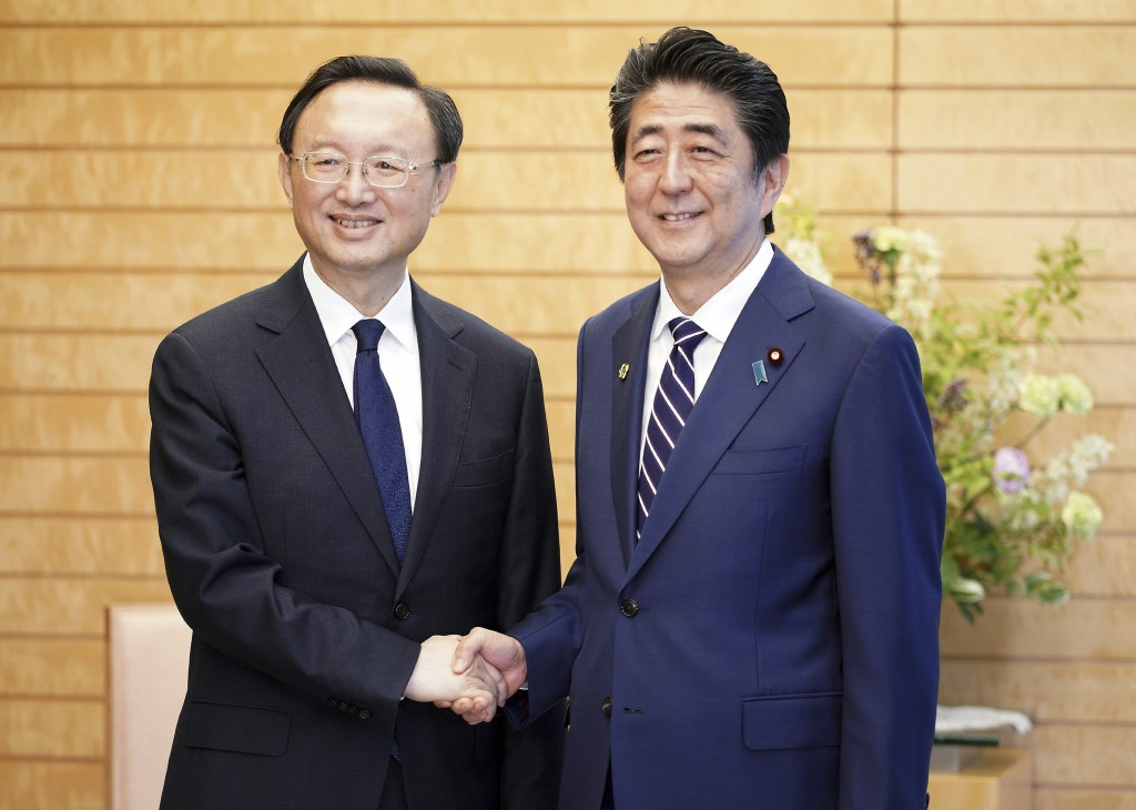 Chinese State Councilor Yang Jiechi, left, and Japanese Prime Minister Shinzo Abe, right, shake hands at Abe's official residence in Tokyo Friday, May