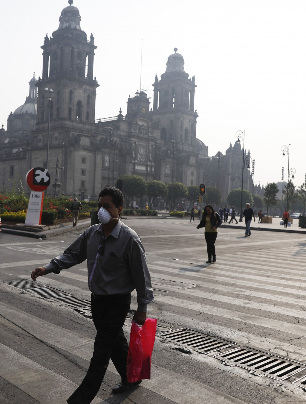 A man wearing a face mask crosses a street by the Metropolitan Cathedral, shrouded by haze, in the Zocalo, Mexico City's main square, Thursday, May 16