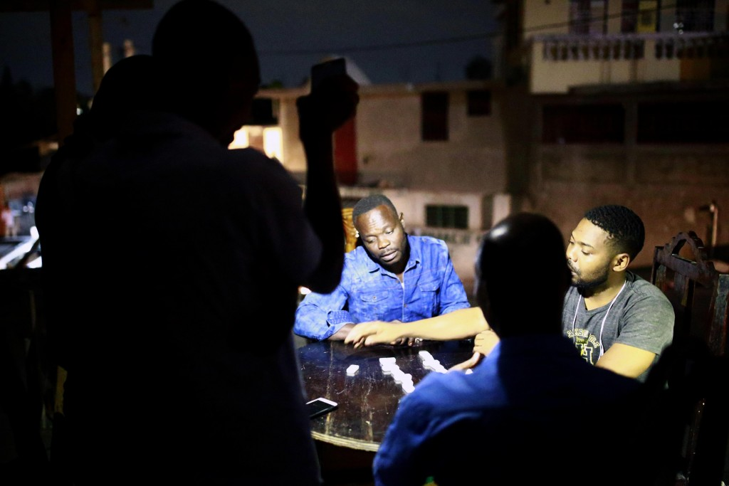 In this April 16, 2019 photo, a man holds up his mobile phone to light others playing dominos in Petion-Ville, Haiti. Nighttime activity has ground to