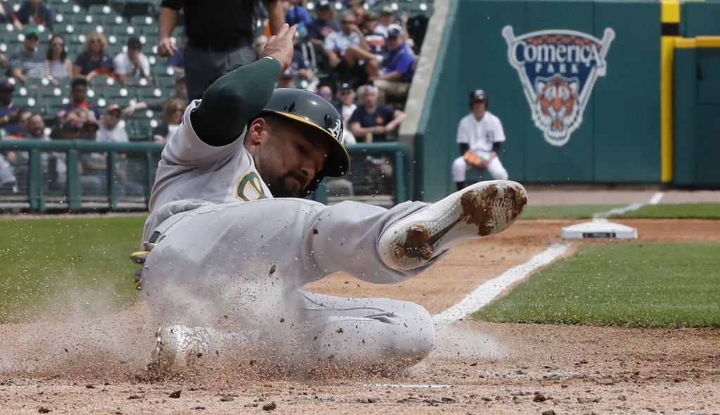 Oakland Athletics' Marcus Semien scores from third on a wild pitch during the third inning of a baseball game against the Detroit Tigers, Thursday, Ma