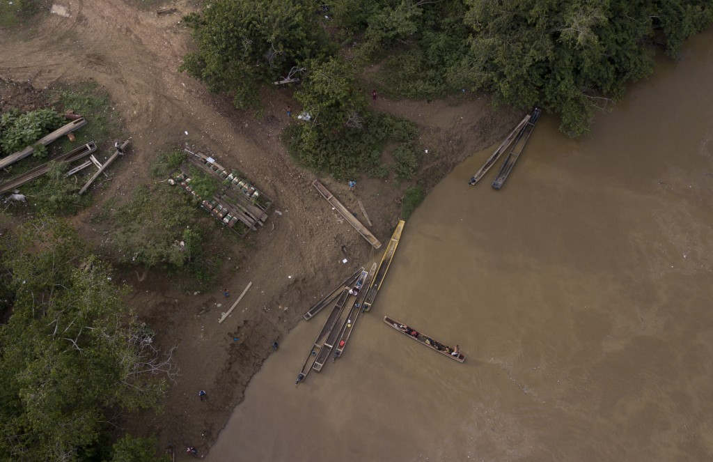 In this May 10, 2019 photo, a group of migrants are boated across the Chucunaque river as they arrive in Peñitas, Darien Province, Panama. Darien's ri