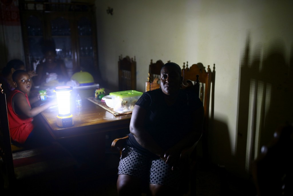 In the April 17, 2019 photo, Jennifer Jean sits with her family in the living room of her home, lit only by camping lantern, in Port-au-Prince, Haiti.