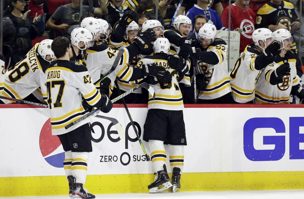 Boston Bruins hug Brad Marchand (63) following Marchand's empty-net goal against the Carolina Hurricanes during the third period in Game 4 of the NHL
