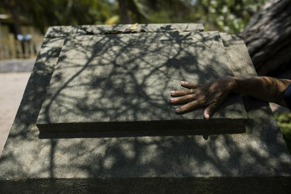 A woman touches a monument that honors a Cuban gue...