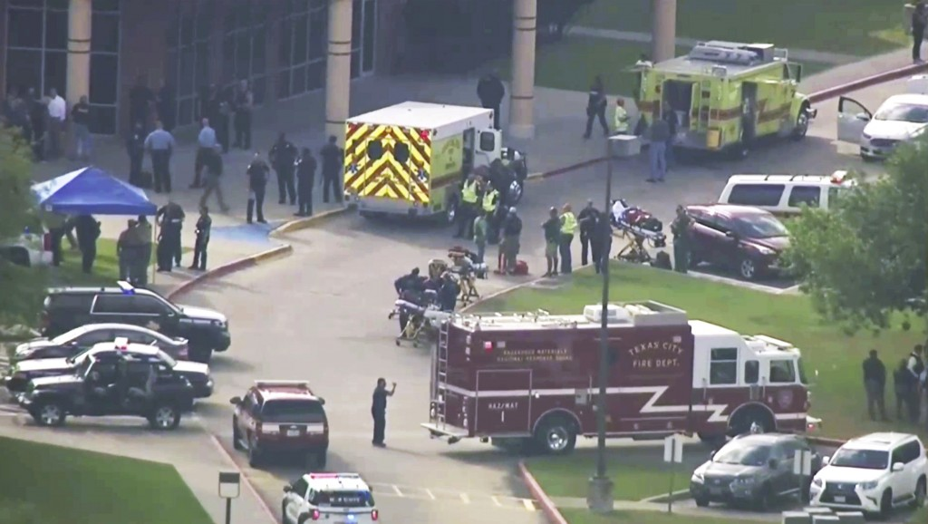 FILE - In this Friday, May 18, 2018 file image taken from video, emergency personnel and law enforcement officers respond to a high school near Housto