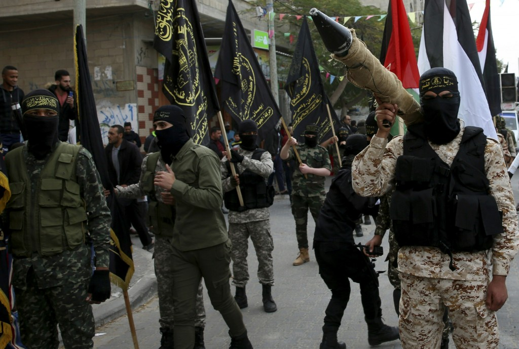 FILE - In this Dec. 22, 2017 file photo, masked members of the Palestinian Al-Quds Brigades, the military wing of the Islamic Jihad group, march with ...