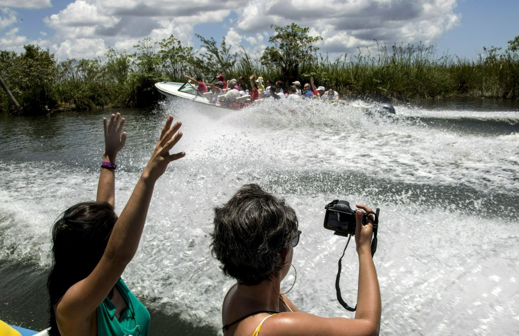 In this May 13, 2019 photo, tourists take photos while being transported by boat to the Laguna del Tesoro, in the Zapata Peninsula, Matanzas, Cuba. Th