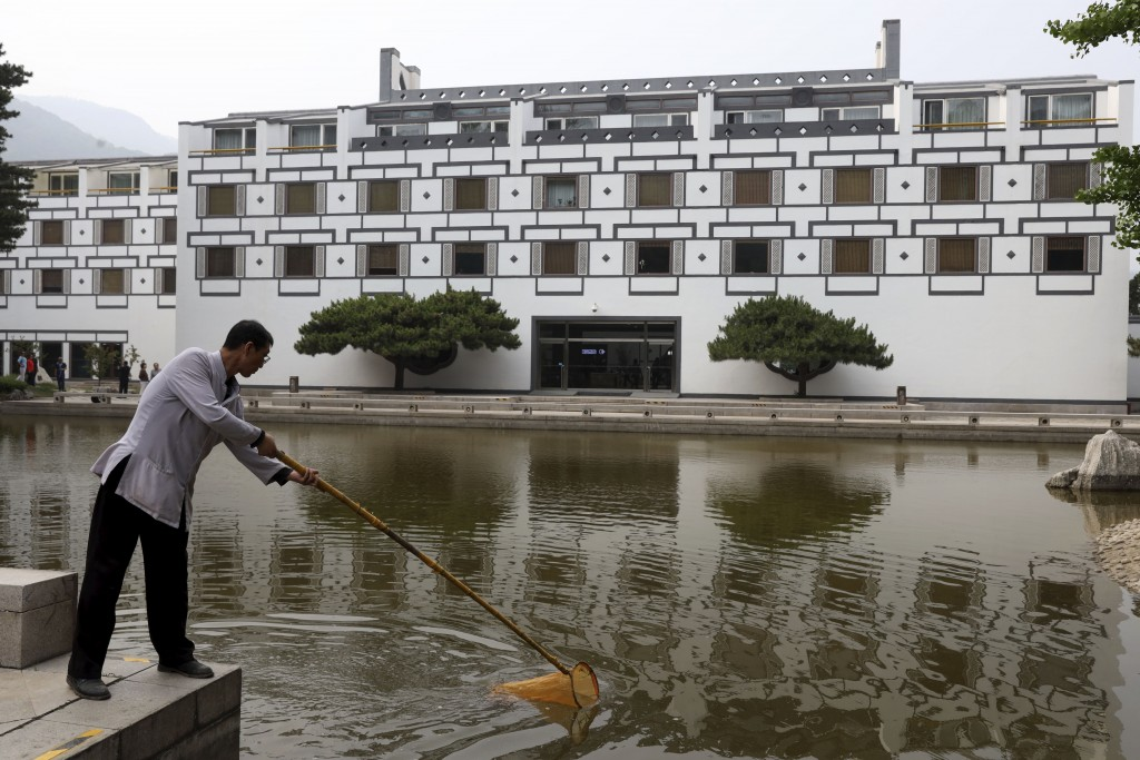 A worker cleans the pond at the Xiangshan hotel designed by Chinese-American architect I.M. Pei and built in 1982 in Beijing, China on Friday, May 17,...