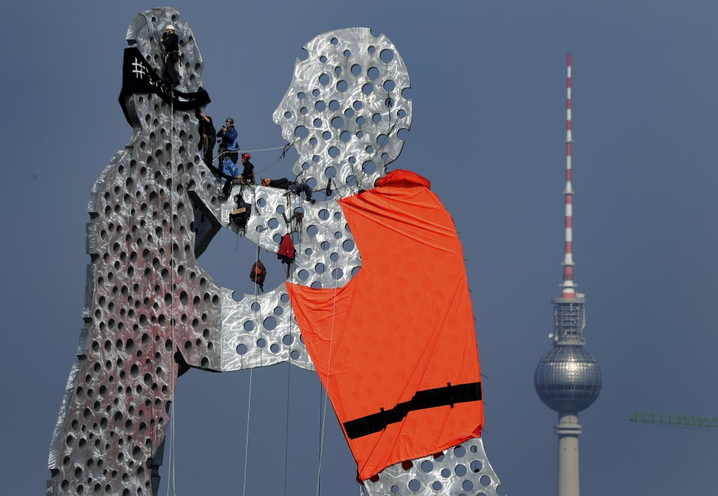 Activists add a life vest to the capital's iconic 'Molecule Man' statue in Berlin, Germany, Friday, May 17, 2019. Protesters climbed the 100-foot tall