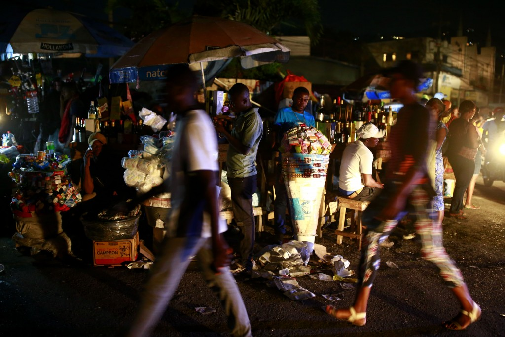 In this April 16, 2019 photo, vendors sit at a street corner as people walk past them, at night in Petion-Ville, Haiti. Since the blackouts hit Haiti,