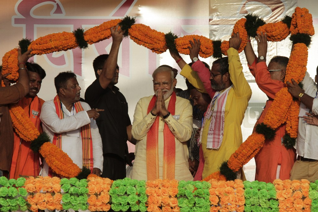FILE- In this Thursday, May 16, 2019 file photo, Indian Prime Minister Narendra Modi, center, is offered a giant floral garland during an election ral