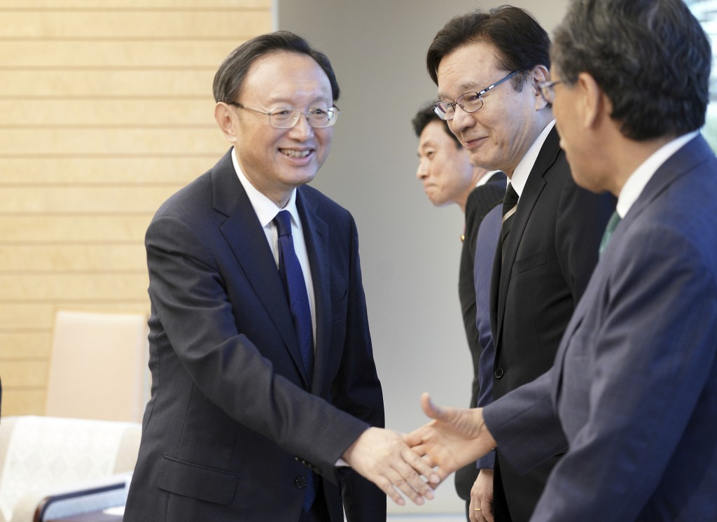 Chinese State Councilor Yang Jiechi, left, and Japanese officials shake hands prior to a meeting with Japanese Prime Minister Shinzo Abe at Abe's offi