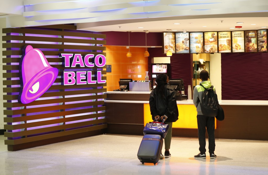 FILE - In this April 19, 2019, file photo, travelers look at a menu at a Taco Bell restaurant inside Miami International Airport in Miami. Taco Bell i