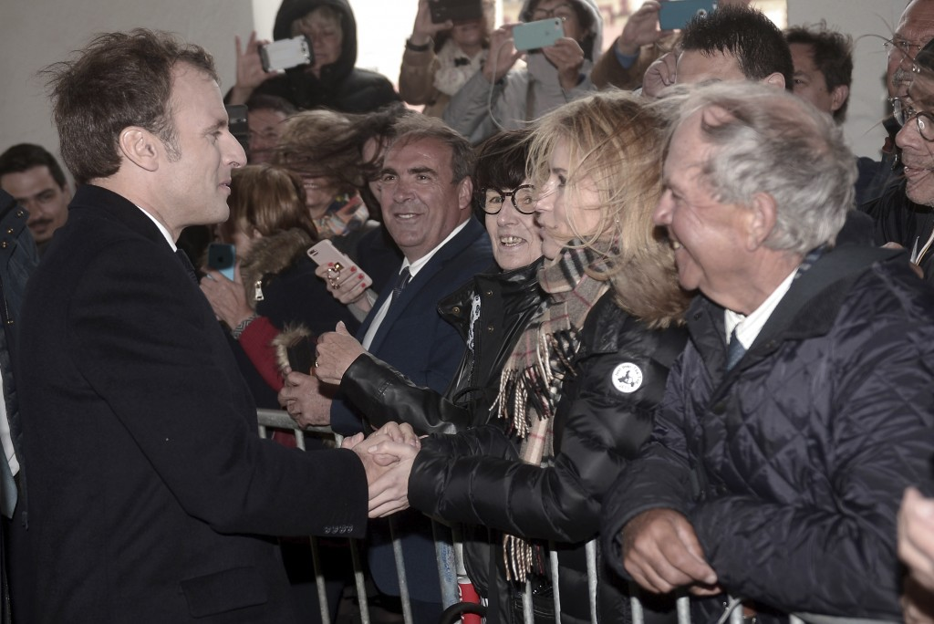 French President Emmanuel Macron, left, shakes hands with residents as he arrives to prepare the upcoming G7 in Biarritz, southwestern France, Friday ...
