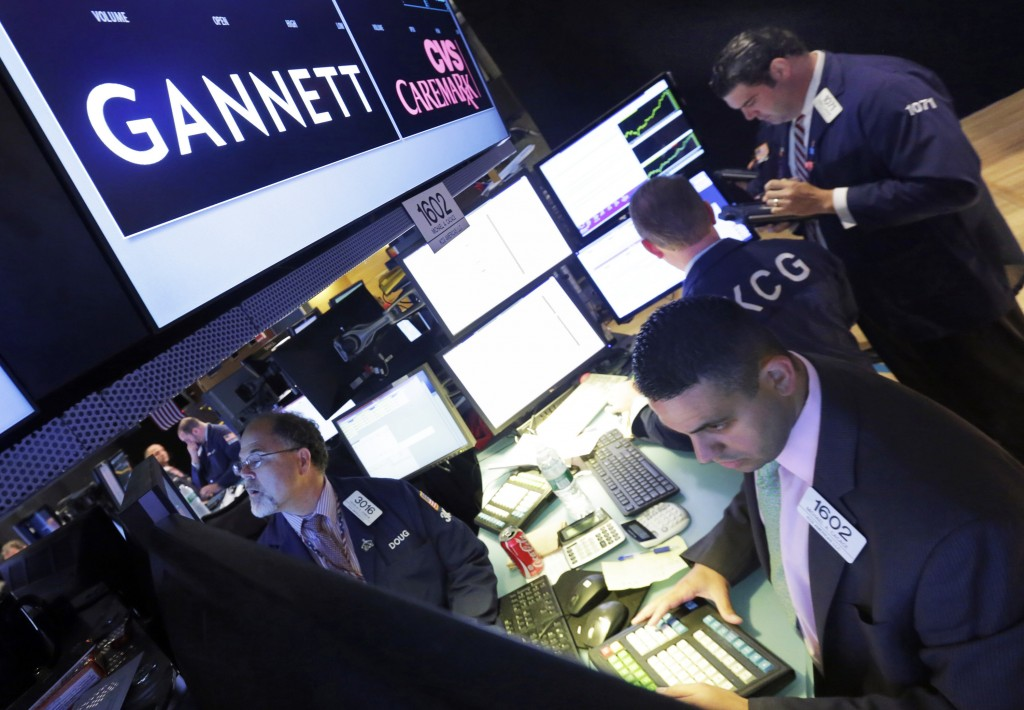 FILE - In this Aug. 5, 2014, file photo, specialist Michael Cacace, foreground right, works at the post that handles Gannett, on the floor of the New ...