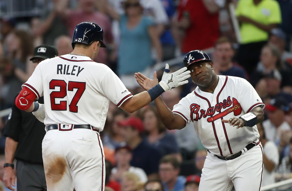 Atlanta Braves rookie Austin Riley (27) celebrates with first base coach Eric Young (2) after driving in a run with a base hit in the third inning of