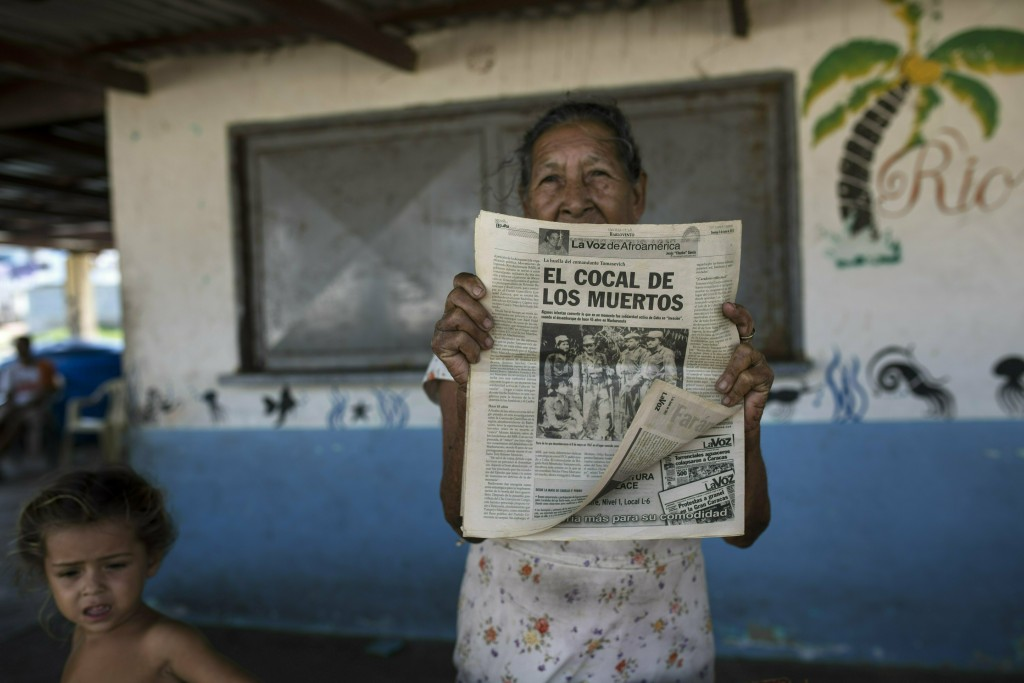 A woman shows a 2012 publication of a local newspaper carrying the story of the 1967 Cuban guerrilla operation in Machurucuto, Venezuela, Sunday, May