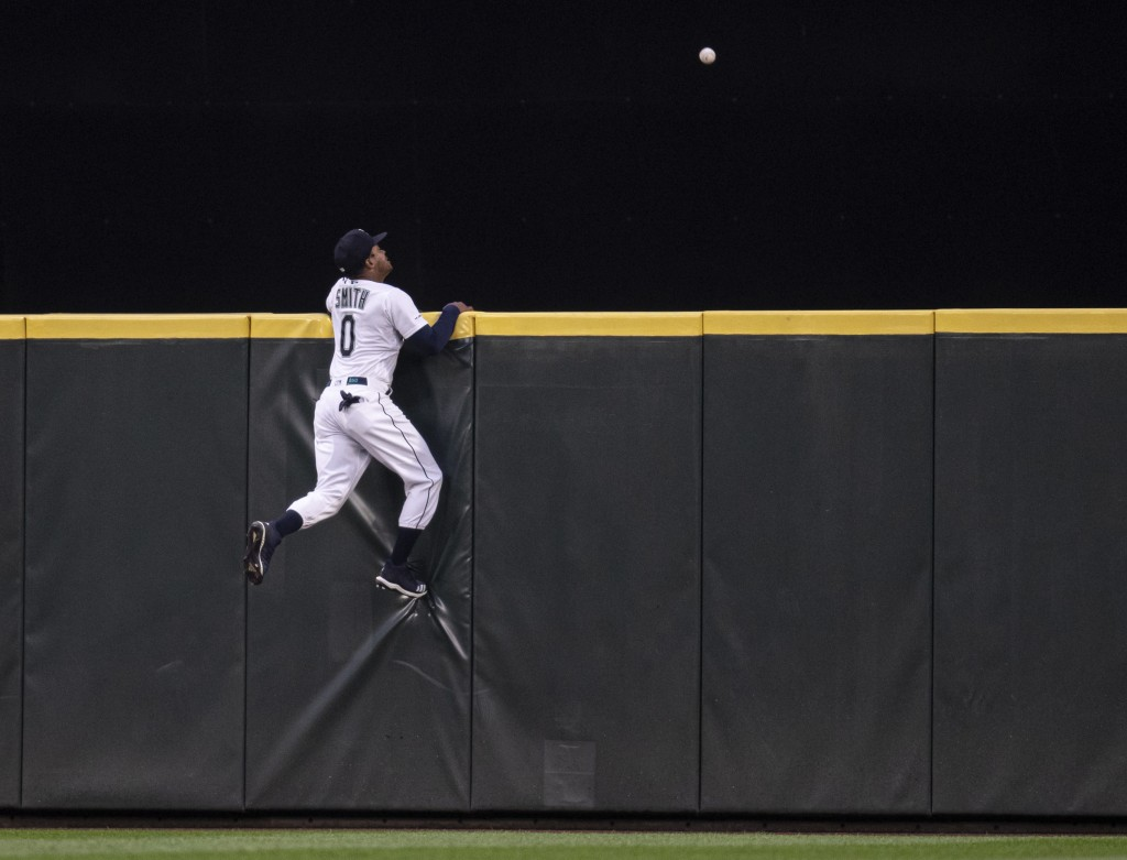 Seattle Mariners center fielder Mallex Smith climbs the wall, but can't get to a three-run home run by Minnesota Twins' Byron Buxton off  pitcher Erik