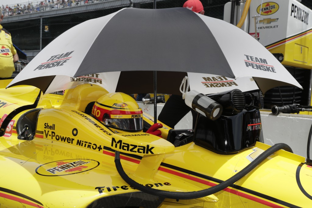 Helio Castroneves, of Brazil, sits in his car under an umbrella during practice for the Indianapolis 500 IndyCar auto race at Indianapolis Motor Speed