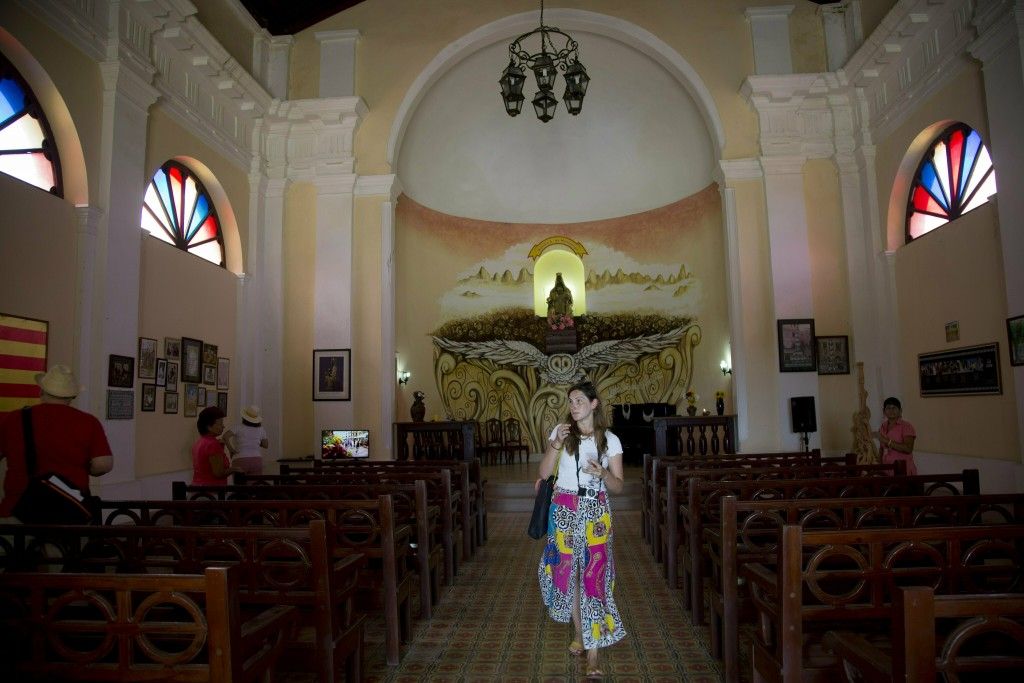 In this May 11, 2019 photo, a tourist walks through a Spanish-style church at the Hermitage of Monserrate, in Matanzas, Cuba. In total, Cuba drew 4.7