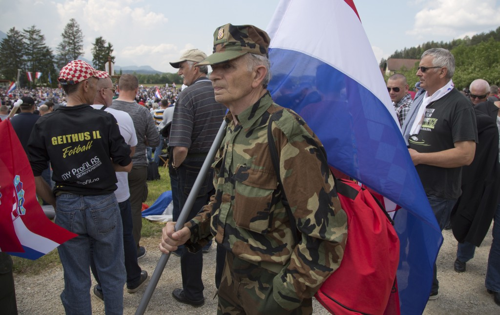 FILE - In this Saturday, May 12, 2018 file photo, a uniformed man carries a Croatian flag during a commemoration ceremony in Bleiburg, Austria. Thousa...