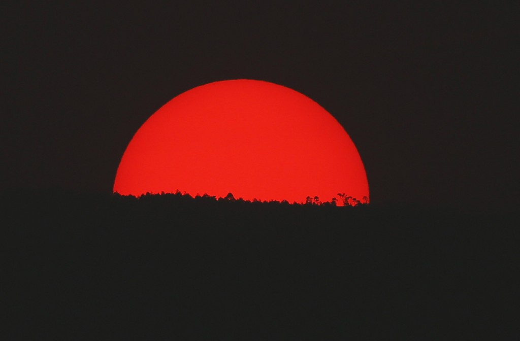 In this May 13, 2019 photo, tinted blood red by a thick cloud of smoke and pollution, the sun sets on the mountains above Mexico City. Mexico City's g