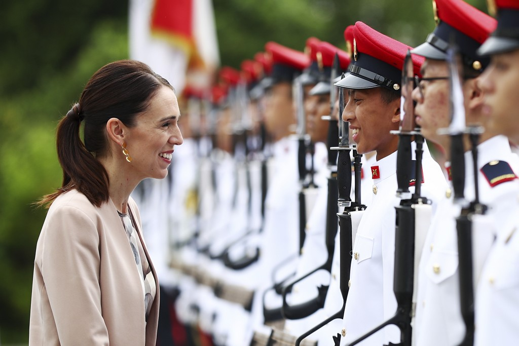 New Zealand's Prime Minister Jacinda Ardern speaks with a member of the honor guard during a welcome ceremony at the Istana or presidential palace in