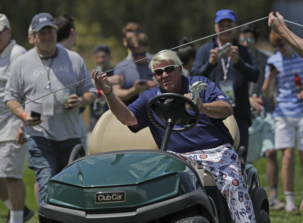 John Daly lifts a rope to get his golf cart to the 12th tee during the first round of the PGA Championship golf tournament, Thursday, May 16, 2019, at