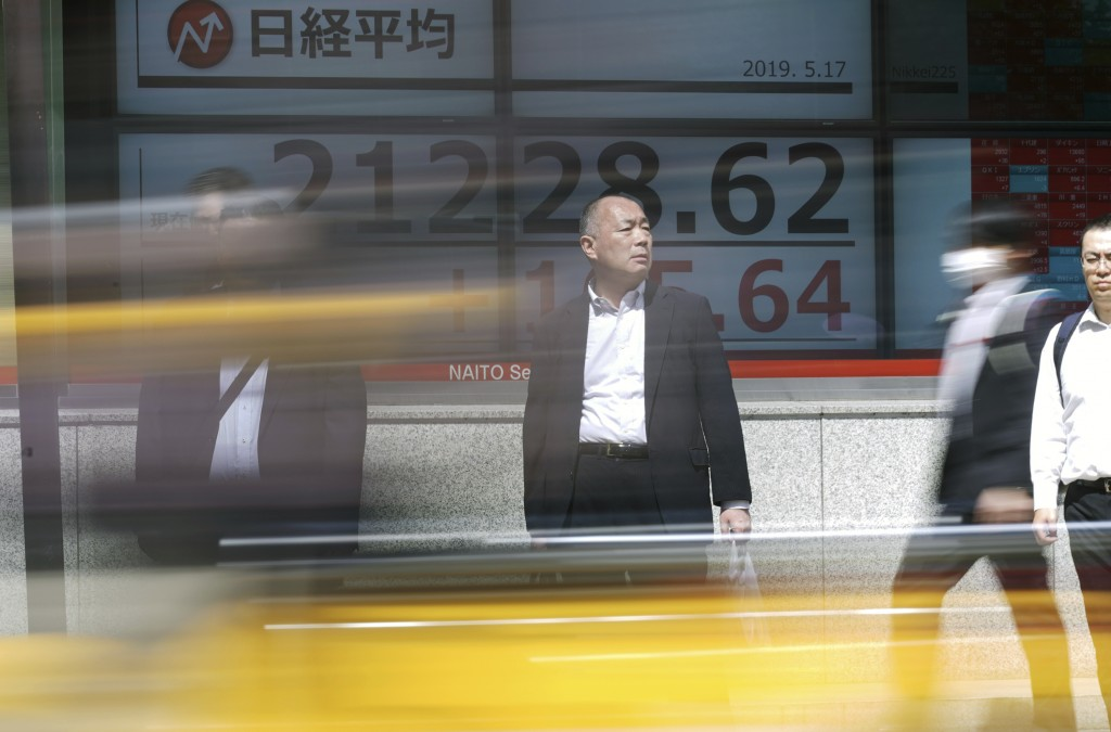 People walk past an electronic stock board showing Japan's Nikkei 225 index at a securities firm in Tokyo Friday, May 17, 2019. Asian stocks were mixe...