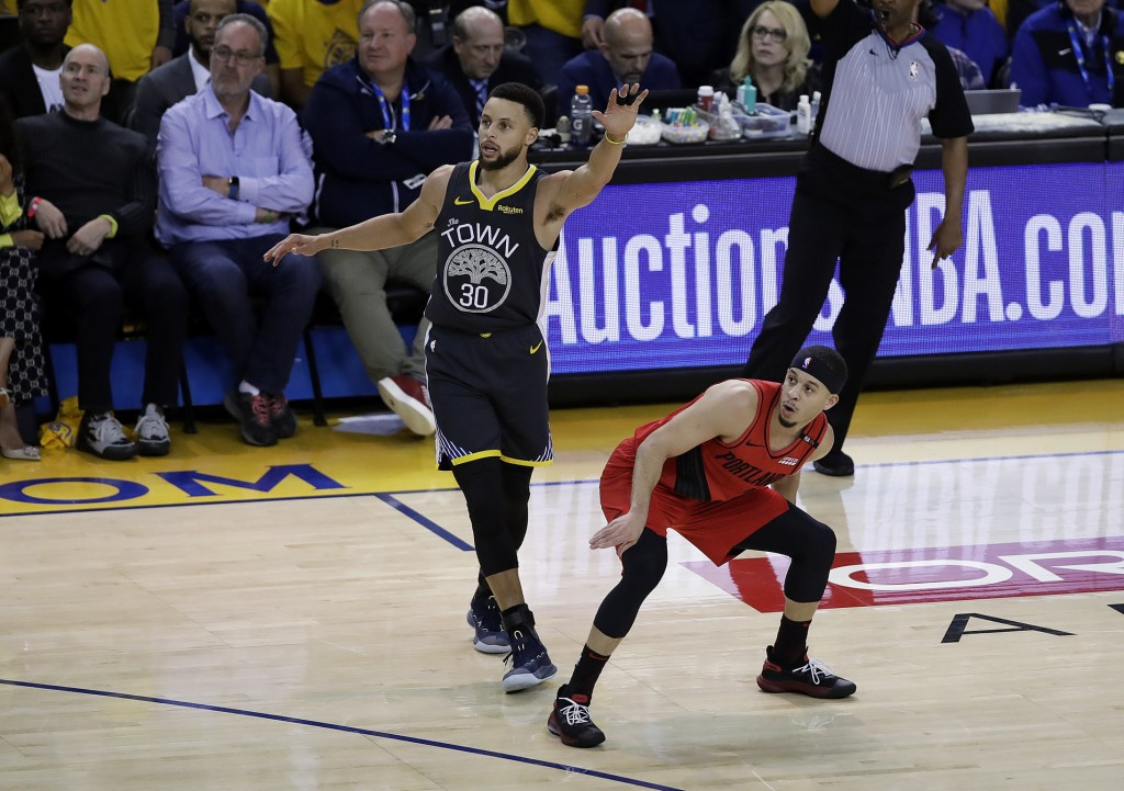 Portland Trail Blazers guard Seth Curry, right, watches his shot next to Golden State Warriors guard Stephen Curry during the first half of Game 2 of
