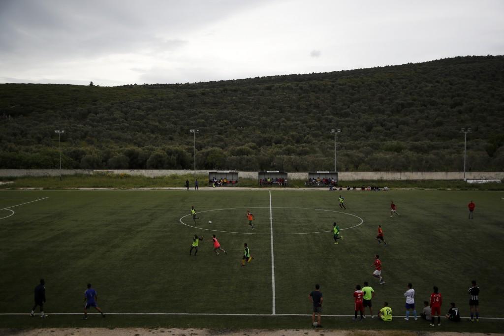 In this Saturday, May 4, 2019, African team and Afghan migrants play a friendly game at a soccer field, in Moria village, on the northeastern Aegean i...