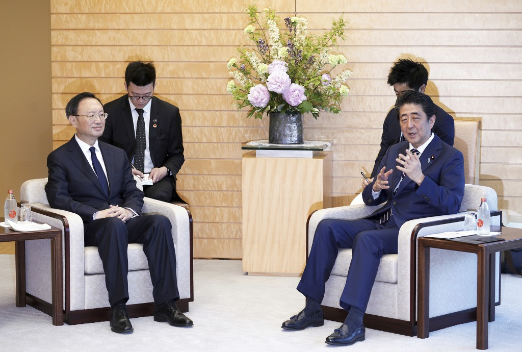 Chinese State Councilor Yang Jiechi, left, and Japanese Prime Minister Shinzo Abe, right, speak at Abe's official residence in Tokyo Friday, May 17, 2