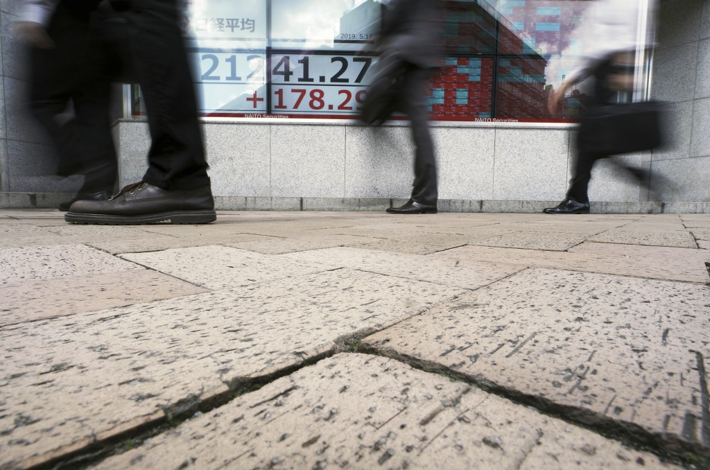 People walk past an electronic stock board showing Japan's Nikkei 225 index at a securities firm in Tokyo Friday, May 17, 2019. Asian stocks were mixe