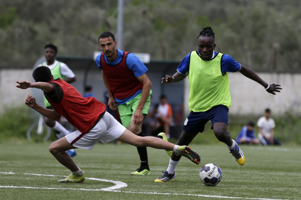 In this Saturday, May 4, 2019, Francis Kalombo from Congo, right, controls the ball during a friendly match between African team and Afghan migrants a