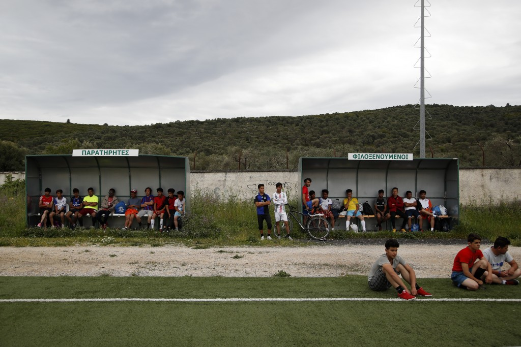 In this Saturday, May 4, 2019, migrants watch a friendly soccer match between African team and Afghan migrants at a soccer field, in Moria village, on...