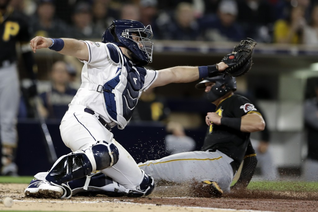 San Diego Padres catcher Austin Hedges is late with the tag as Pittsburgh Pirates' Kevin Newman scores from third during the fifth inning of a basebal