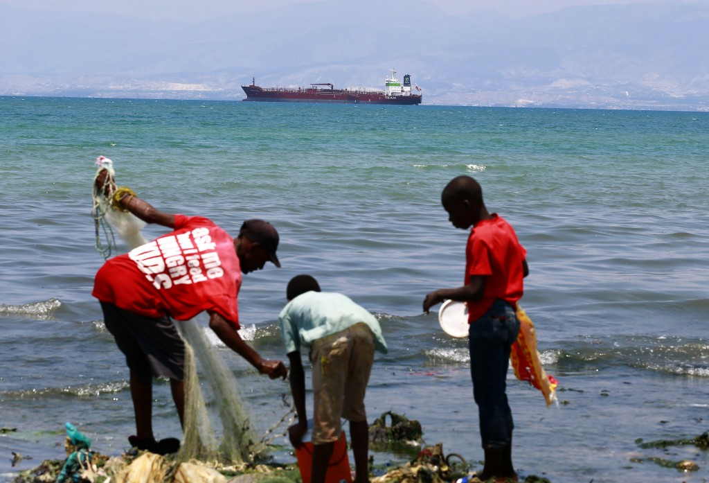 In this April 16, 2019 photo, residents fish while a tanker waits out in the bay to unload its cargo at the Thor terminal in Carrefour, a district of