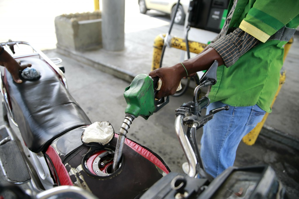 In this April 16, 2019 photo, a gas station attendant fills the gas tank of a motorcycle in Port-au-Prince, Haiti. Through the Venezuelan aid program