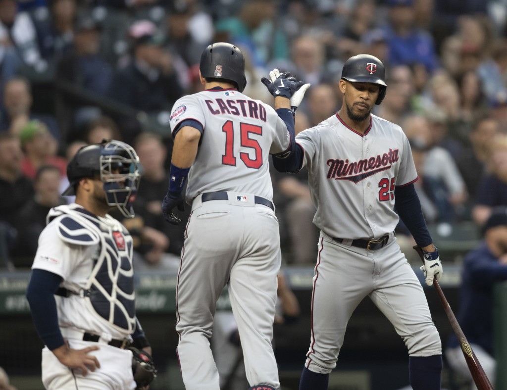 Minnesota Twins' Jason Castro (15) is congratulated by Byron Buxton after hitting a solo home run off of Seattle Mariners starting pitcher Erik Swanso