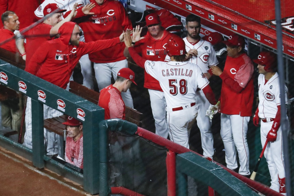 Cincinnati Reds' Luis Castillo (58) celebrates in the dugout after scoring on a wild pitch by Chicago Cubs starting pitcher Jose Quintana during the f