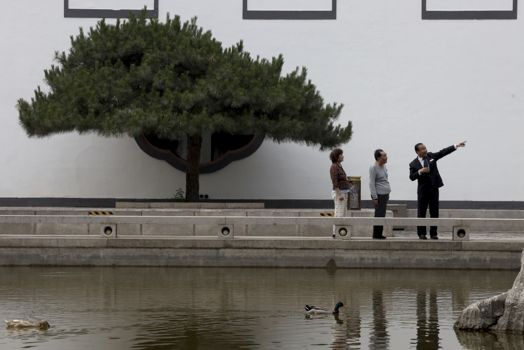 Hotel staff gives directions to visitors as ducks swim in a pond at the Xiangshan hotel designed by Chinese-American architect I.M. Pei and built in 1...